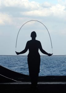 woman near ocean with jump rope