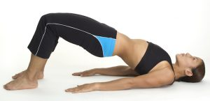 woman laying on yoga mat excising her lower abs