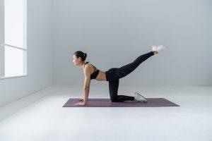 woman on yoga mat doing inner thigh lifts